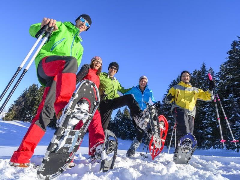 gutgelaunte Wandergruppe mit Schneeschuhen